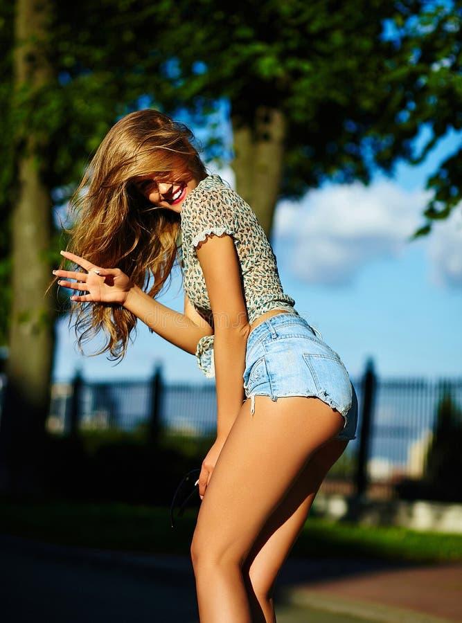 Modieus glimlachend meisje in heldere toevallige doek in jeansborrels in openlucht stock foto's