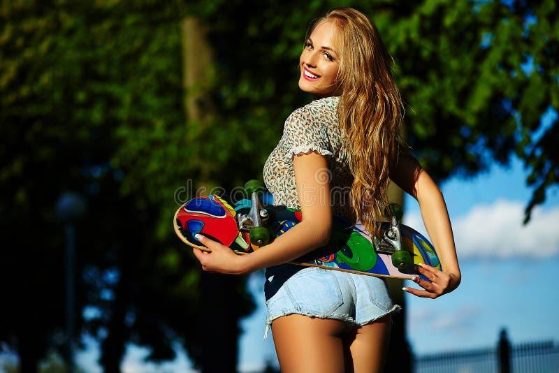Modieus glimlachend meisje in heldere toevallige doek in jeansborrels in openlucht stock foto
