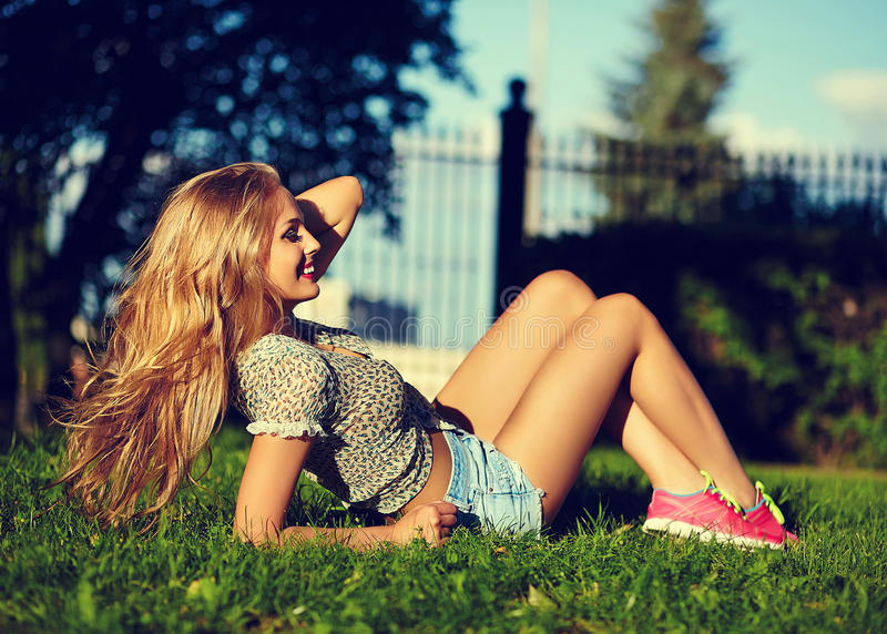 Modieus glimlachend meisje in heldere toevallige doek in jeansborrels in openlucht royalty-vrije stock afbeelding