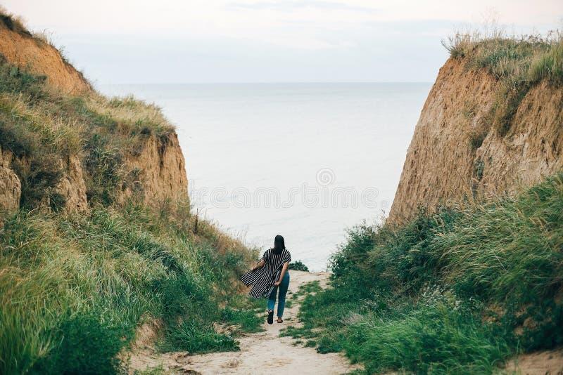 Modieus hipstermeisje die aan overzees tussen zandige klippen met gras bij zonsondergang lopen Gelukkige jonge bohovrouw die trop stock foto's