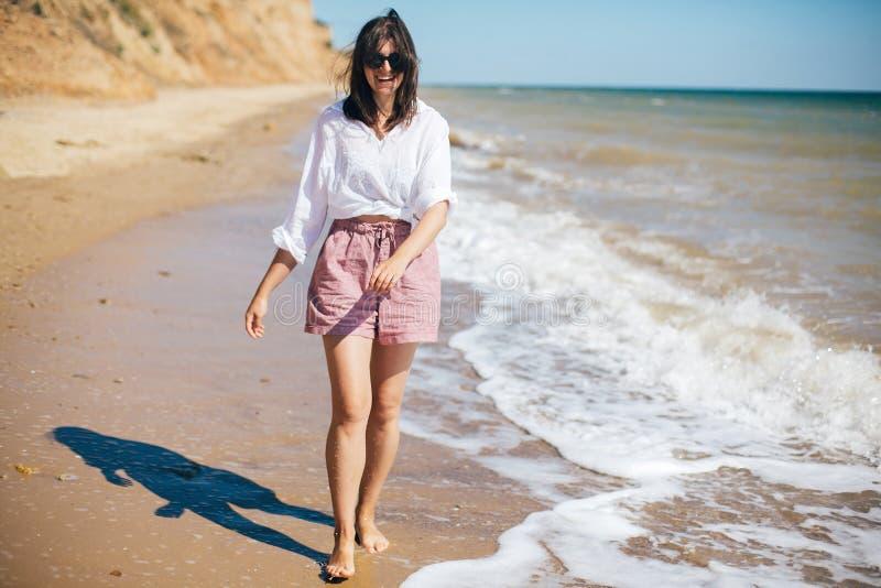 Modieus hipstermeisje die bij strand en het glimlachen lopen De vakantie van de zomer Gelukkige jonge bohovrouw die en van zonnig royalty-vrije stock afbeelding