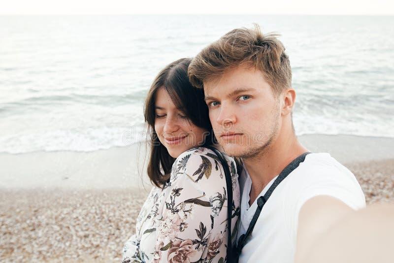 Modieus hipsterpaar die selfie op strand bij avondoverzees nemen De vakantie van de zomer Portret van gelukkige jonge familie op  royalty-vrije stock fotografie