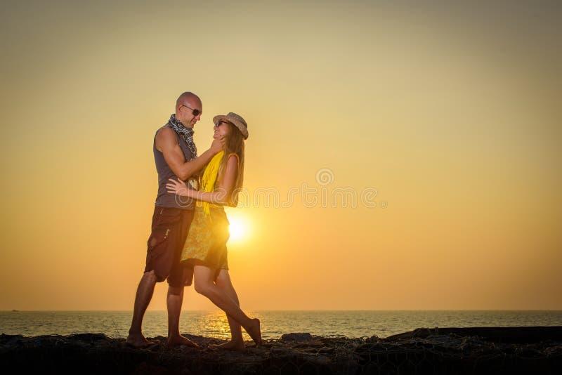 Modieus houdend van paar die elkaar op het strand koesteren bij zonsondergang Man en vrouw in de reis van vakantiewittebroodsweke royalty-vrije stock foto's