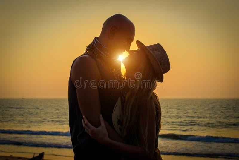 Modieus houdend van paar die elkaar op het strand koesteren bij zonsondergang Man en vrouw in de reis van vakantiewittebroodsweke royalty-vrije stock foto