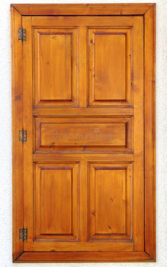 Modieus houten venster op steenmuur stock afbeeldingen