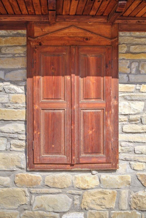 Modieus houten venster op steenmuur stock fotografie