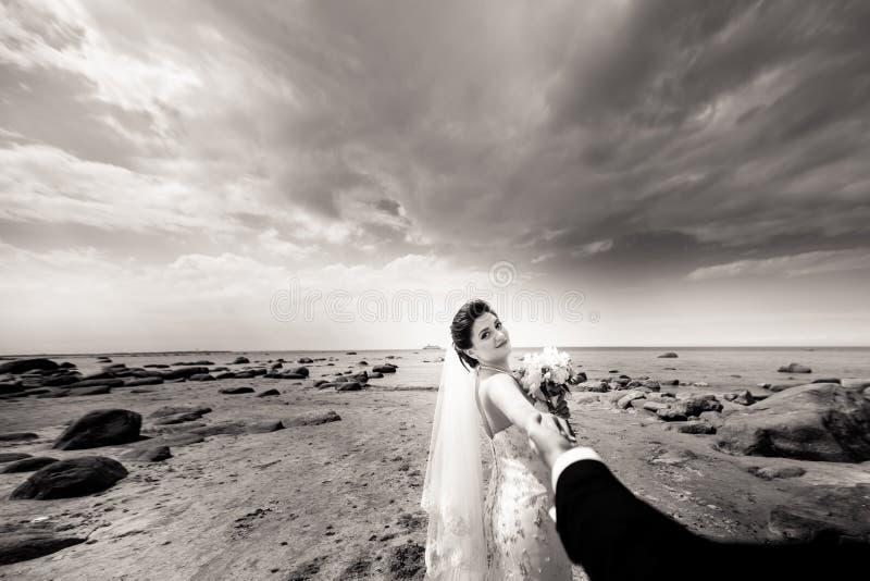 Modieus huwelijkspaar die zich op overzeese kust bevinden De jonggehuwden lopen door het overzees Rebecca 36 royalty-vrije stock foto