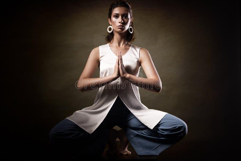 Modieus jong atletisch meisje in modieuze kleren, die yogaasanas in de studio tonen Schoonheidsgezicht en lichaamsgezondheid stock fotografie