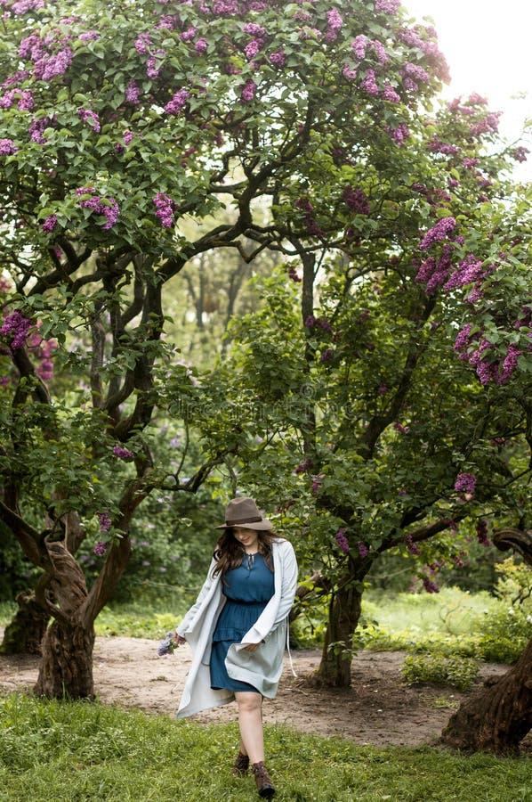 Modieus jong meisje die in de tuin van tot bloei komende seringen lopen stock afbeeldingen
