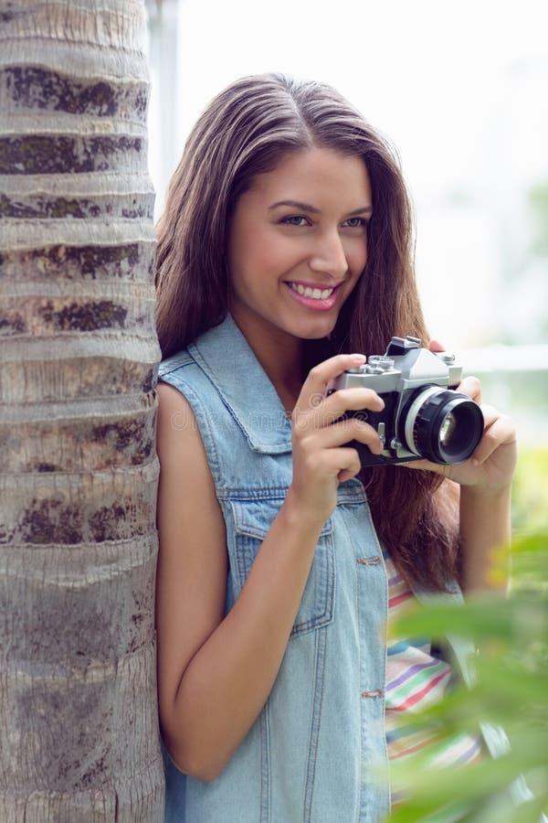 Modieus jong meisje die foto's buiten nemen royalty-vrije stock afbeelding