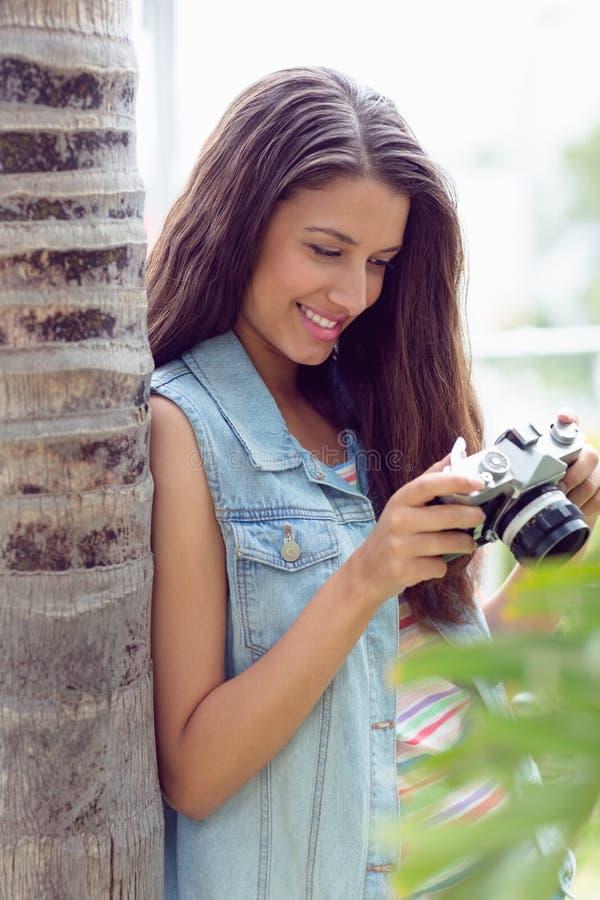 Modieus jong meisje die haar camera bekijken stock fotografie