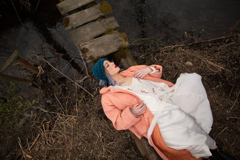 Modieus jong meisje die op de rivierkust rusten, die op een kleine houten brug liggen stock foto's