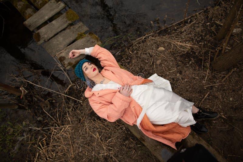 Modieus jong meisje die op de rivierkust rusten, die op een kleine houten brug liggen royalty-vrije stock fotografie