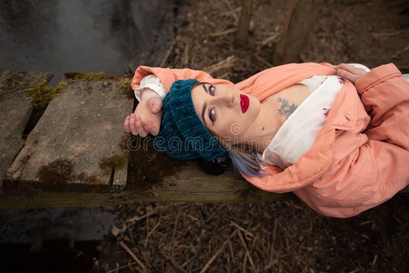 Modieus jong meisje die op de rivierkust rusten, die op een kleine houten brug liggen stock foto