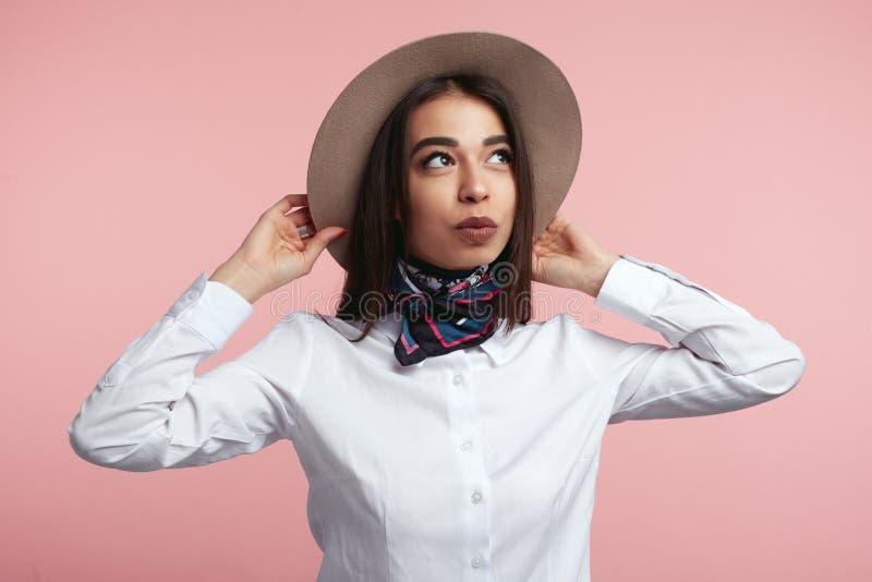 Modieus jong meisje die wit overhemd en modieuze sjaal dragen, haar hoed houden en weg over roze studiomuur kijken stock afbeeldingen