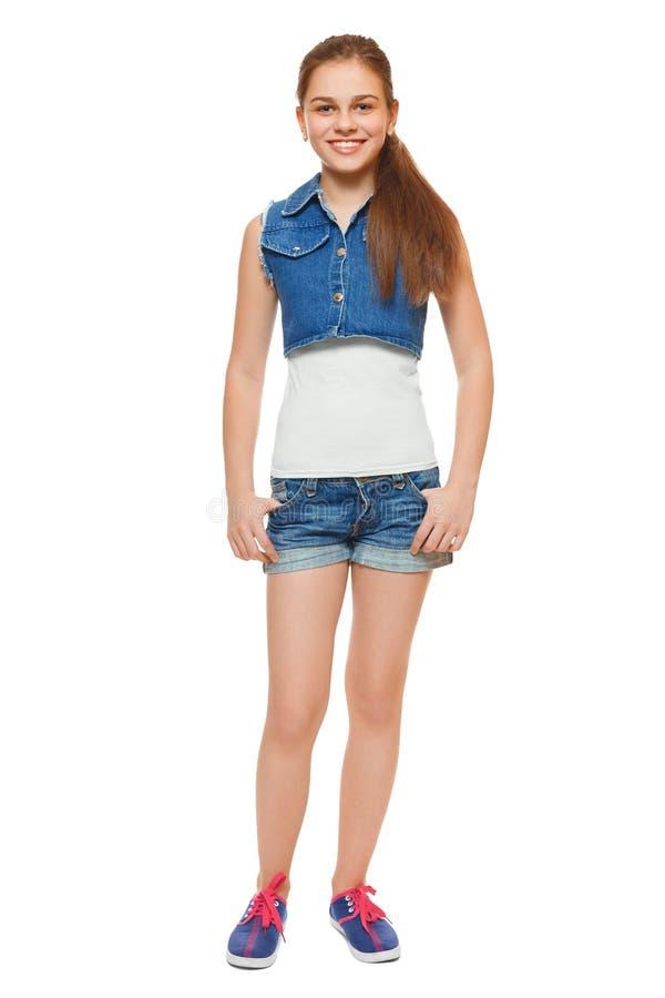 Modieus jong meisje in een van het jeansvest en denim borrels De tiener van de straatstijl, levensstijl, op witte achtergrond wor royalty-vrije stock foto
