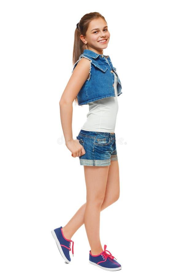 Modieus jong meisje in een van het jeansvest en denim borrels De tiener van de straatstijl, levensstijl, op witte achtergrond wor stock fotografie