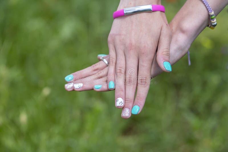 Modieus jong meisje met een manicure en een armband tegen de achtergrond van aard Manier, levensstijl, schoonheid, kleding stock fotografie