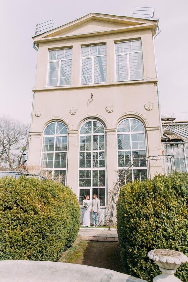 Modieus jong paar dichtbij het oude beige huis met kolommen en grote uitstekende vensters Romantisch Huwelijk in Parijs royalty-vrije stock afbeeldingen