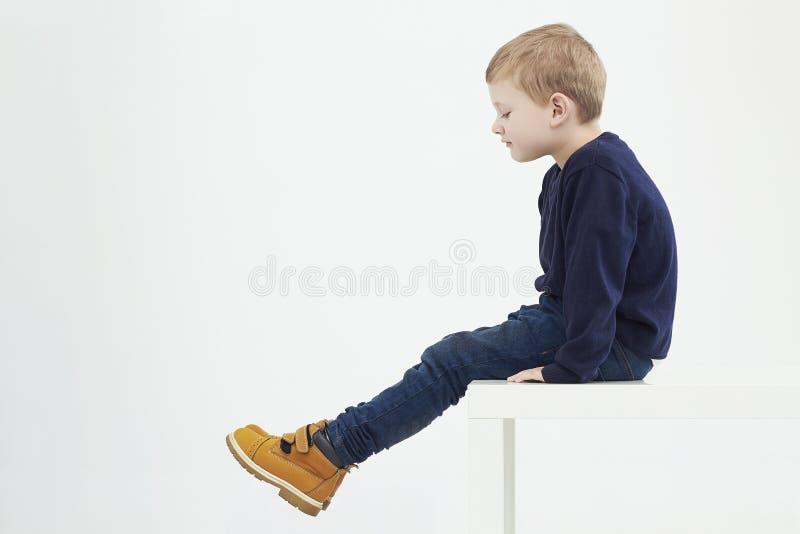 Modieus kind in gele laarzen De jonge geitjes van de manier weinig jongenszitting op een lijst stock afbeeldingen