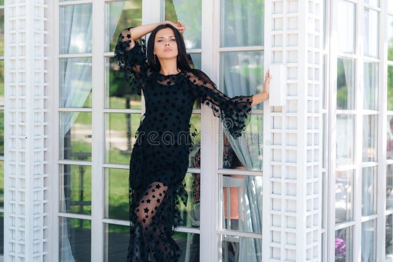 Modieus lang brunette met mooie lange benen die in een zwarte kledingsbuitenkant dichtbij een glasmuur stellen stock foto's