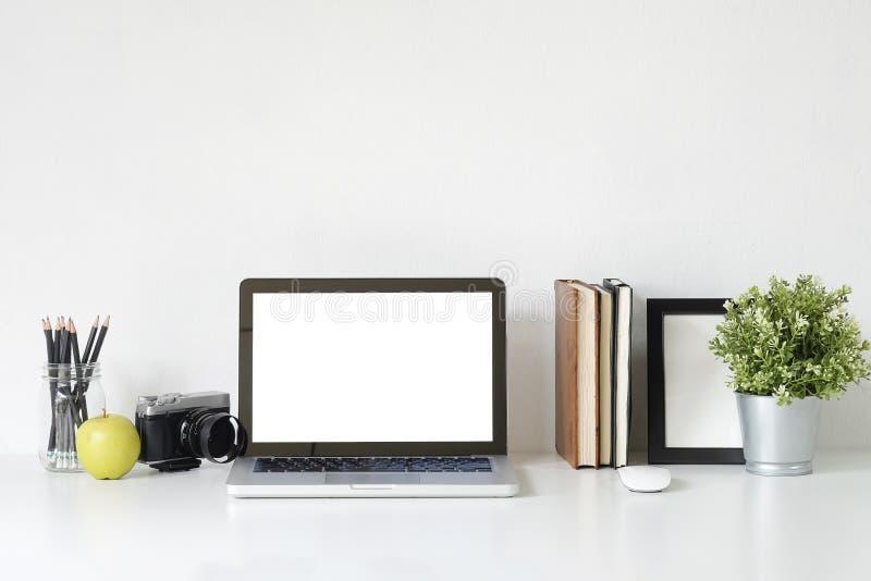 Modieus laptop van het lijstmodel computer, camera, boek en fotokader op wit bureau met bureaulevering stock afbeelding