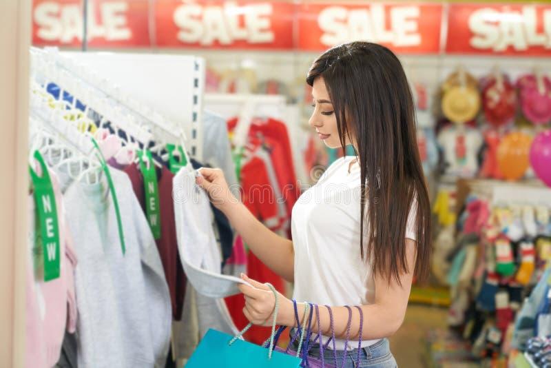 Modieus meisje die blouse in kledingsopslag kiezen royalty-vrije stock foto