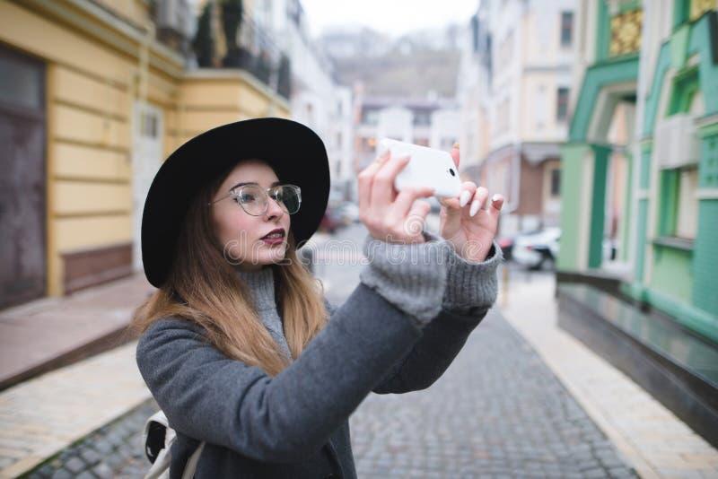 Modieus meisje die een straatfoto op de telefoon fotograferen Een toeristenmeisje maakt een foto van architectuur op een smartpho stock foto's