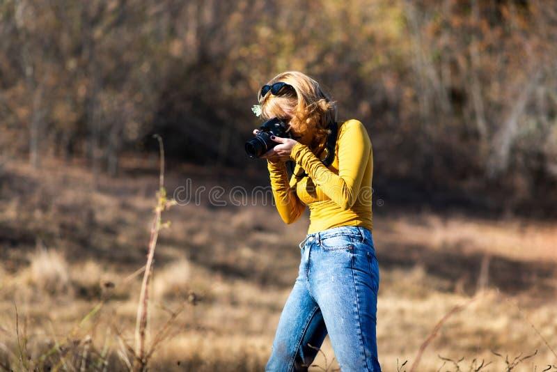 Modieus meisje die foto's in openlucht nemen stock foto