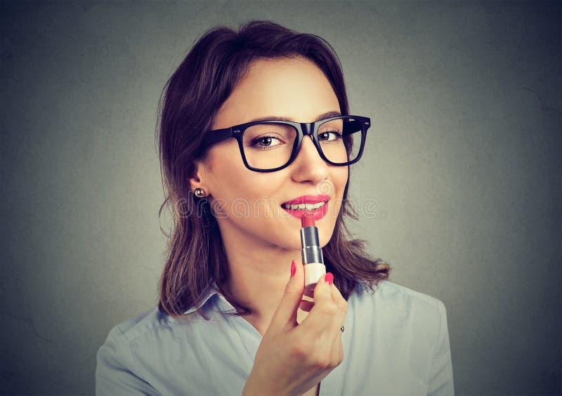 Modieus meisje die rode lippenstift toepassen royalty-vrije stock foto
