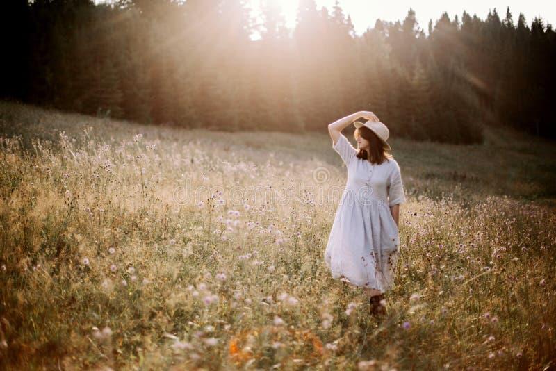 Modieus meisje die in rustieke kleding in wildflowers in zonnige weide in bergen lopen Bohovrouw het ontspannen in plattelandsblo stock foto