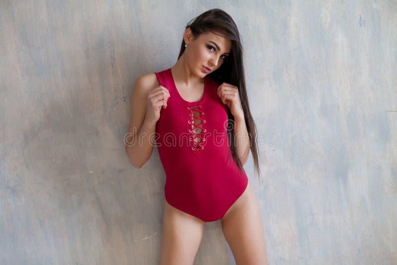 Modieus meisje in het rode lichaam stellen op grijze achtergrond stock afbeeldingen