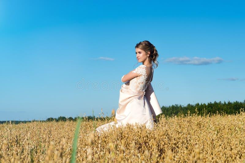 Modieus meisje in mooie beige kleding in gebiedsrogge stock foto's