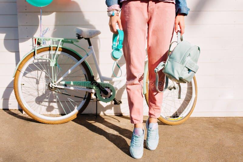 Modieus meisje in in roze broek en tennisschoenen die zich op tiptoe holdingsrugzak en hoofdtelefoons bevinden Het slanke vrouw d stock fotografie