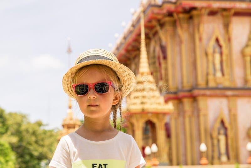 Modieus meisje in strohoed en zonnebril die openlucht dichtbijgelegen Wat Chalong-TEMPEL in Phuket, Thailand, Azië bevinden zich  royalty-vrije stock foto's
