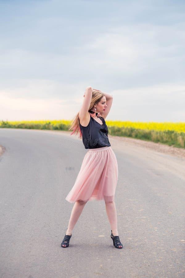 Modieus meisjesmodel in een rok van Tulle en het zwarte hoogste stellen op de weg royalty-vrije stock fotografie