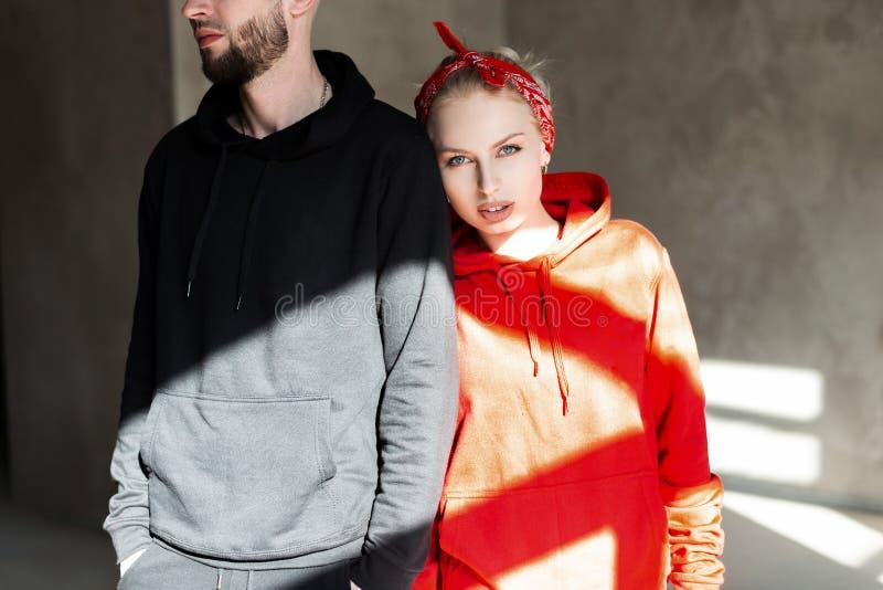 Modieus mooi modieus paar in manier zwarte en rode hoodie binnen met zonlicht Mooie hipstervrouw in een rode hoodie royalty-vrije stock foto's