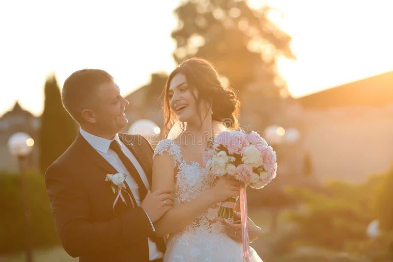 Modieus paar van gelukkige jonggehuwden die in het park op hun huwelijksdag stellen De perfecte paarbruid, verzorgt grappige grap stock foto's