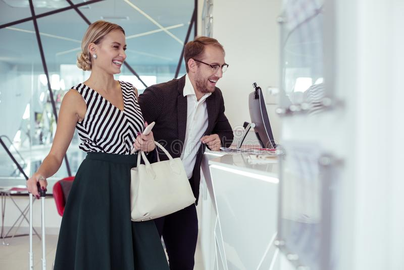 Modieus paar van zakenlieden die met receptionnist communiceren royalty-vrije stock foto's