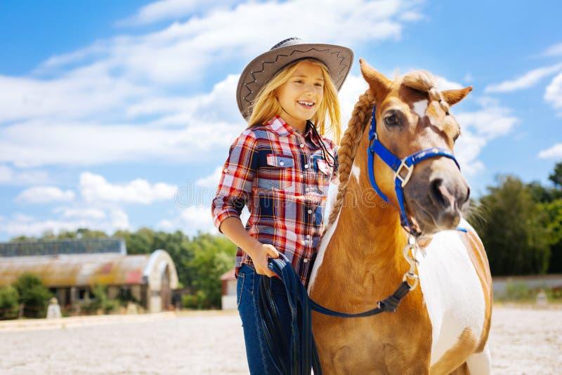 Modieus prettig meisje die zich dichtbij weinig poney bevinden stock afbeeldingen