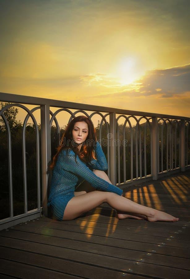 Modieus roodharige in blauwe blouse en lange benen die op een houten brug bepalen Mooi meisje met het lange haar stellen, in open royalty-vrije stock foto's