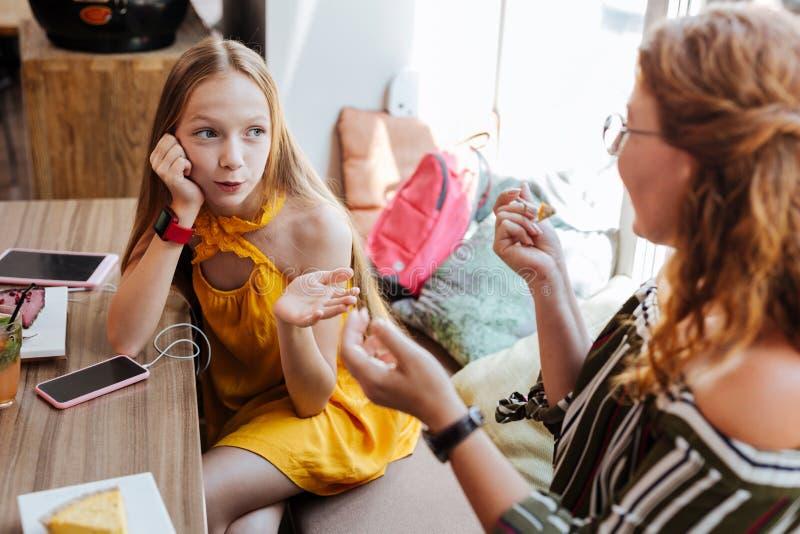 Modieus schoolmeisje die gele kledingszitting in koffie met moeder dragen royalty-vrije stock afbeeldingen
