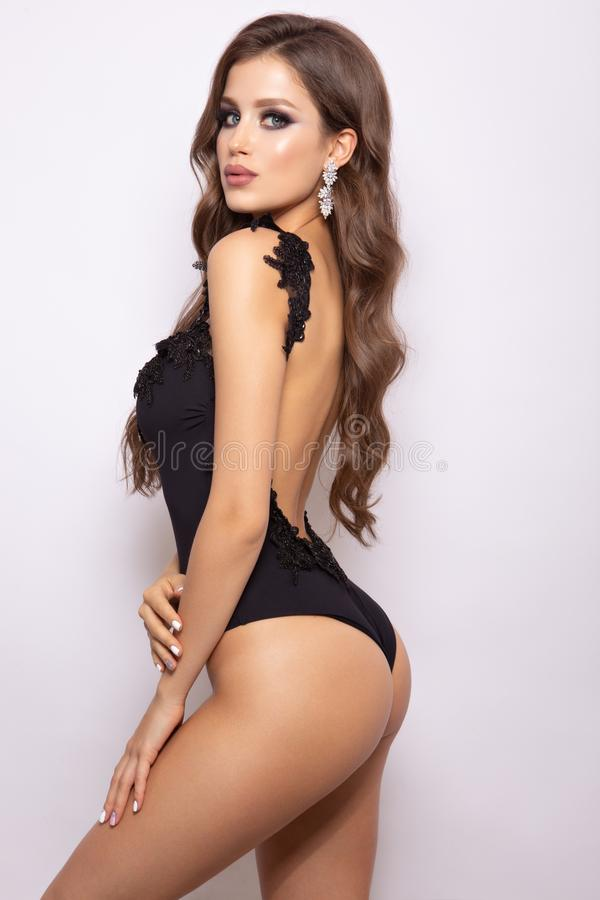 Modieus sexy meisje in een zwart die zwempak op een wightachtergrond wordt geïsoleerd stock foto