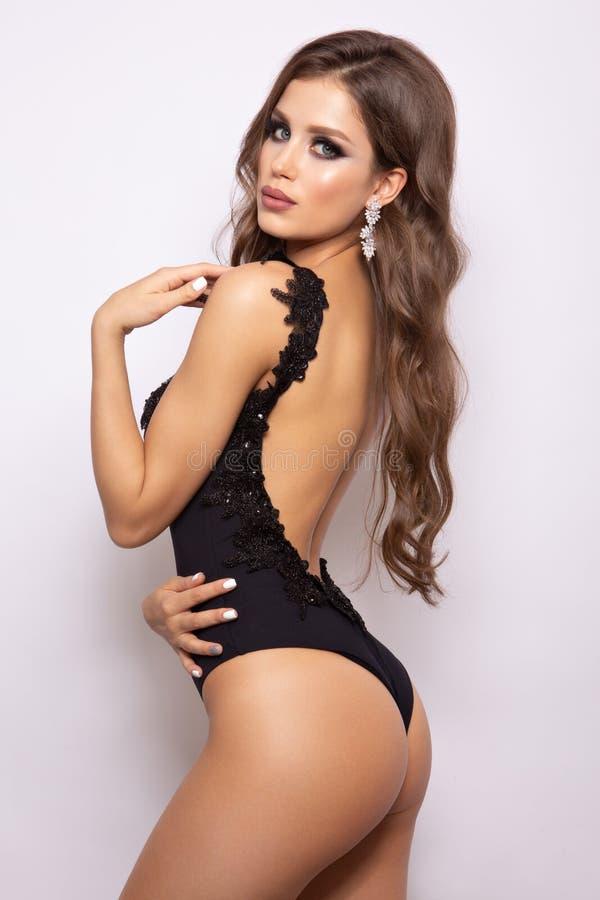 Modieus sexy meisje in een zwart die zwempak op een wightachtergrond wordt geïsoleerd stock afbeeldingen
