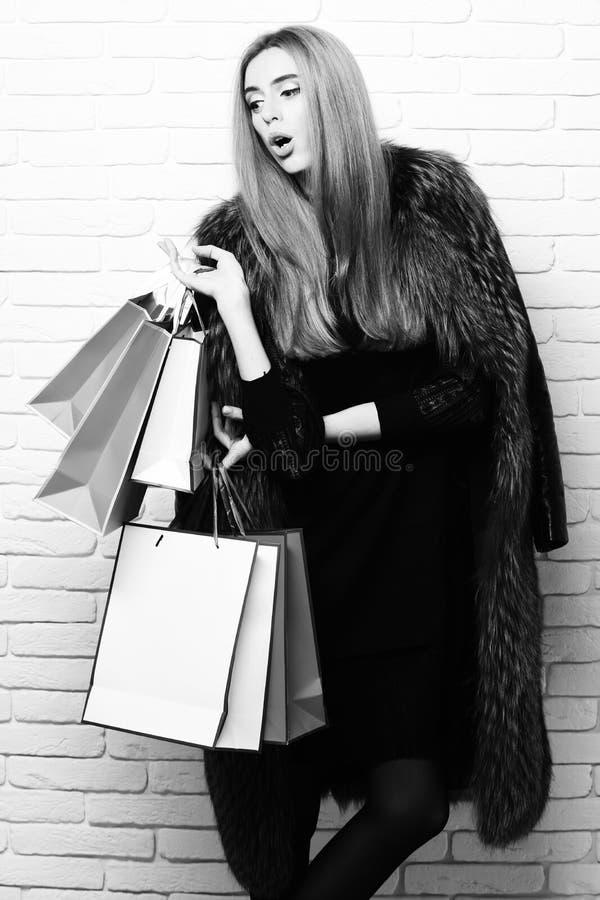 Modieus sexy mooi vrouw of meisje met mooi blondehaar in taillelaag van het bont van Bourgondië met zwarte kleding en stock foto