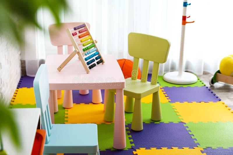 Modieus speelkamerbinnenland met speelgoed en meubilair stock foto's