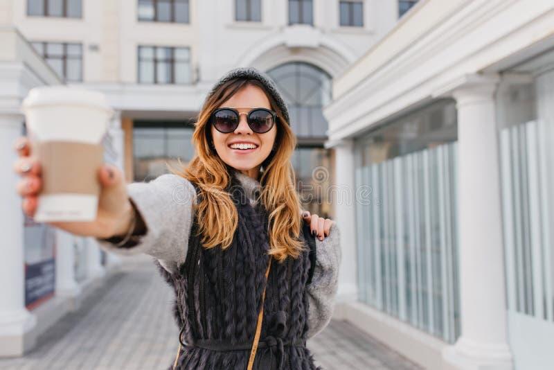 Modieus stadsportret van het glimlachen van blije jonge vrouw het uitrekken zich koffie om naar camera te gaan Goedemorgen van mo stock afbeelding
