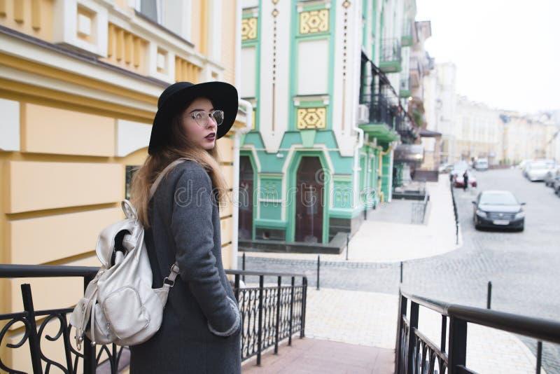 Modieus toeristenmeisje die in de mooie oude stad lopen en de camera onderzoeken royalty-vrije stock foto's