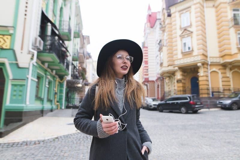 Modieus toeristenmeisje die door de straten van de oude stad met hoofdtelefoons en glimlachen wandelen stock afbeeldingen