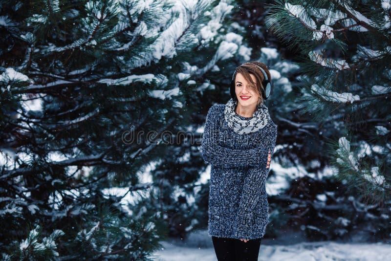Modieus vrolijk meisje in een sweater in het de winterbos stock foto